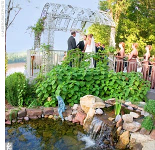 The couple wed outdoors atop a cliff that overlooked the Missouri River. The altar was simply decorated with a white arch covered in greenery and white flowers.