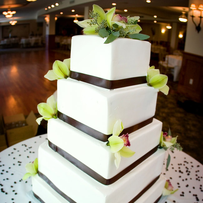 The tall, five-tiered, square cake was frosted with buttercream and made up of five different flavors. Each tier was tied with a chocolate brown ribbon, and cymbidium orchids graced the top two tiers as a final touch.