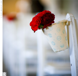 Ashley bought white buckets and spray-mounted fabric on them. Her florist then added bright clusters of red flowers to each one and hung them on the guests' chairs.