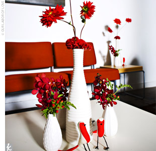 Ashley and Dusty bought simple white vases at Ikea and had their florist create modern minimalist arrangements using bright red carnations, dahlias, and celosia with accents of viburnum berries.