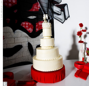 Ashley and Dusty's four-tiered all-white buttercream cake sat on a red stand and was topped with two kitschy bride and groom birds.