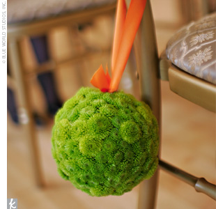 Since the space was quite beautiful on its own, Leigh and David's florist simply provided small pomanders of green button mums to attach to the gold chiavari chairs and tied them off with orange ribbon.
