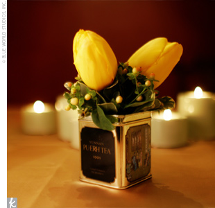 Tea tins filled with purple, orange, and green flowers graced each table at Leigh and David's reception.