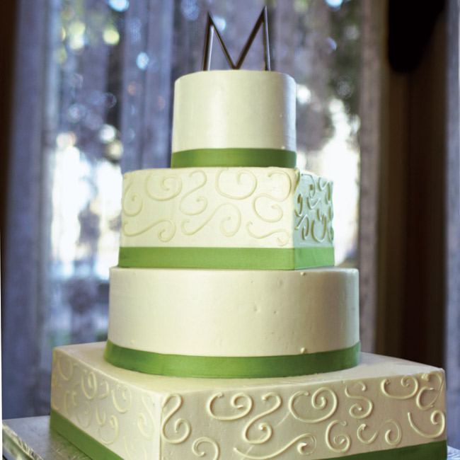 Leigh and David's four-tier cake was covered in delicious buttercream and trimmed with a green band around each tier. The topper was a silver M monogram.