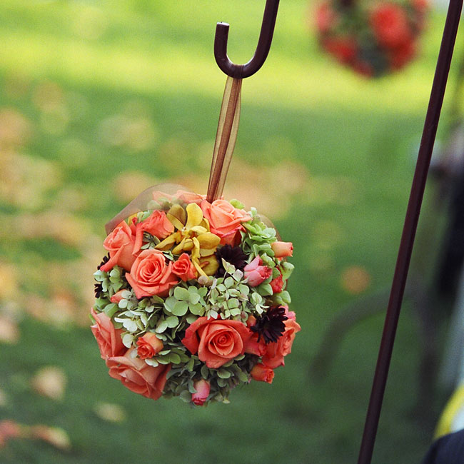 Pomanders hanging from shepherd's hooks added a rustic touch to the ceremony space. Afterward, the pomanders were placed in stone urns and used as centerpieces for the reception.