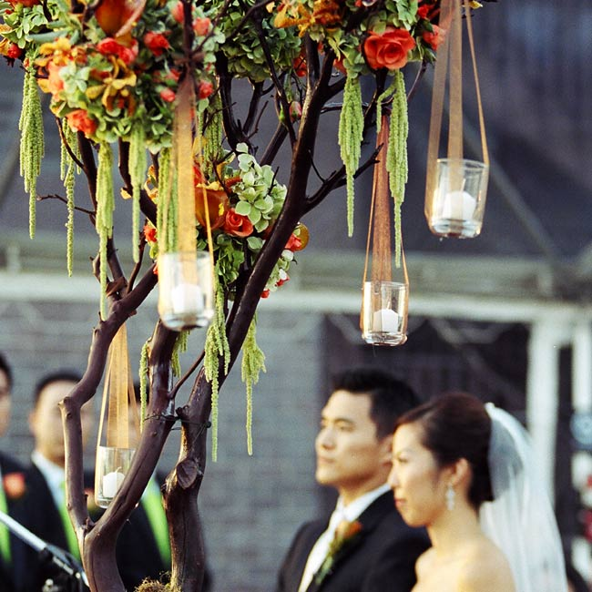 The ceremony space was decorated with two tall manzanita trees in chocolate brown, wooden boxes, and orange roses, mango calla lilies, Singapore orchids, green hydrangeas, and brown micro-daisies.  The trees were later moved to the reception area to be used as part of the centerpieces.