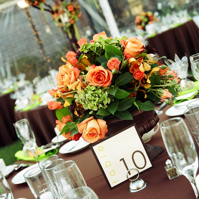 The couple used low and high centerpieces to create a dynamic look on the reception tables. The primary blooms in each arrangement were orange roses, orange spray roses, mango callas, green hydrangeas, Singapore orchids, and brown micro-daisies.