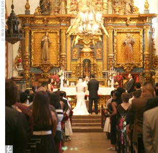 """We loved the San Fernando Mission for its architecture and old world, vintage, Spanish beauty,"" Julie says. The ceremony space features dark wooden beams, distressed flooring, and distressed, dark wood pews with an elaborate altar."