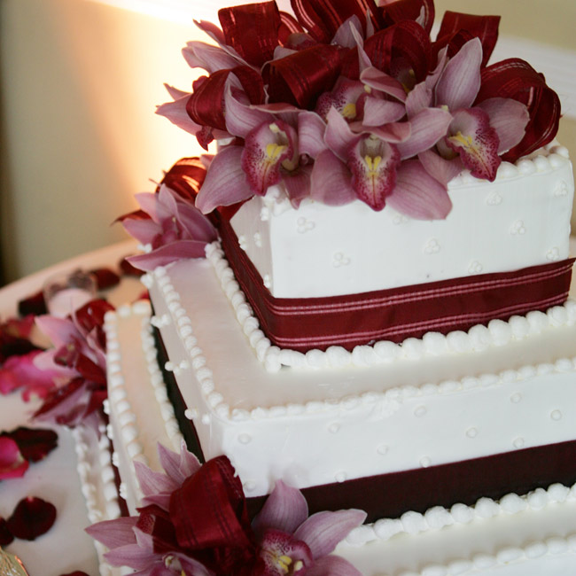 The three-tiered cake was decorated with wine-colored ribbon and burgundy orchids. One tier was chocolate cake with chocolate mousse, another featured marble cake with chocolate mouse, and the last had white chiffon and Bavarian cream filled with fresh strawberries.