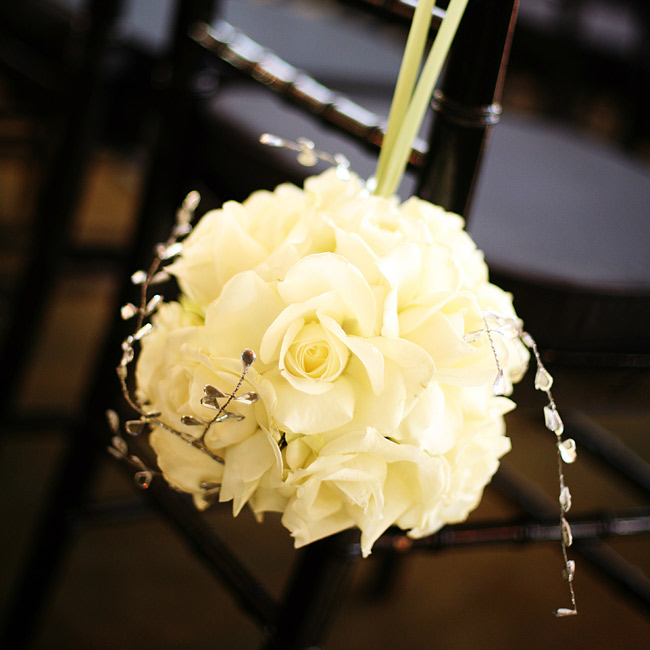 The chairs at the ceremony site were decorated with large kissing balls of white flowers with crystals.