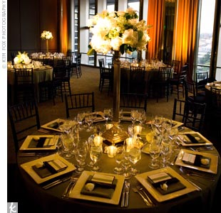 The couple varied the look of their reception tables with alternating high and low centerpieces. The tall arrangements were filled with white and green blooms and included dramatic crystal accents.