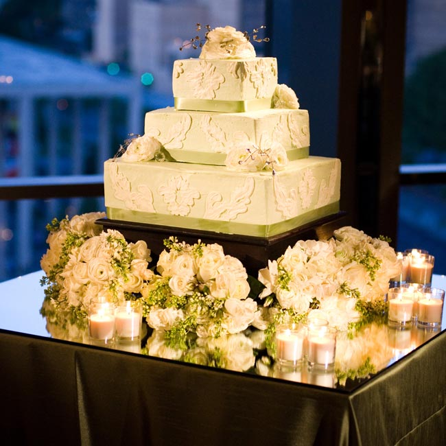 The cake was covered with kiwi green buttercream frosting and white damask piping designed to match the black-and-white design on the invitations. White flowers accented the corners of the middle tier and the top.