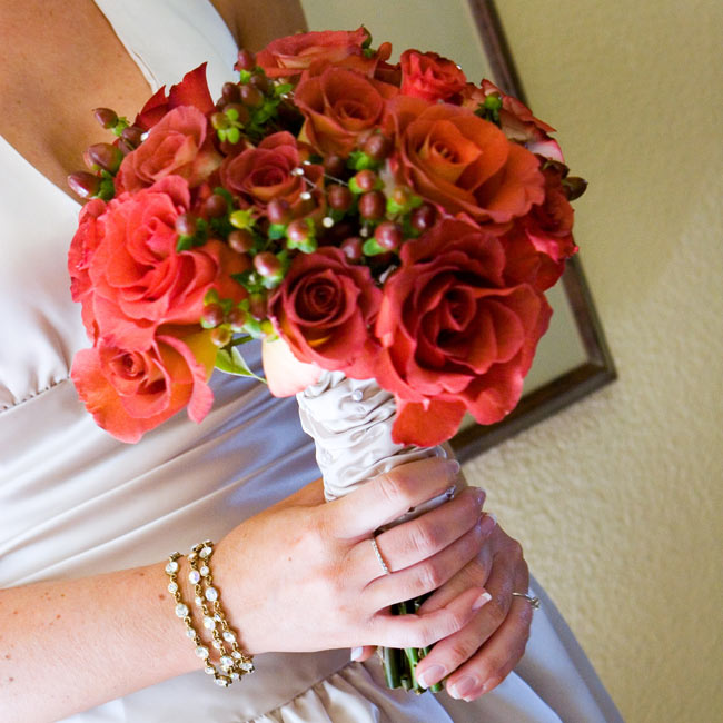 The bride carried a nosegay of russet-colored Leonidas roses (one of Cari's favorite flowers) and red hypericum berries. The bouquet was tied with a strip of champagne satin from Cari's dress.