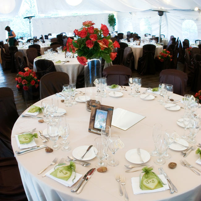 The tented reception space was decorated with large white lanterns. The tables were covered with champagne-colored satin linens and complemented with chocolate-colored satin chair covers.