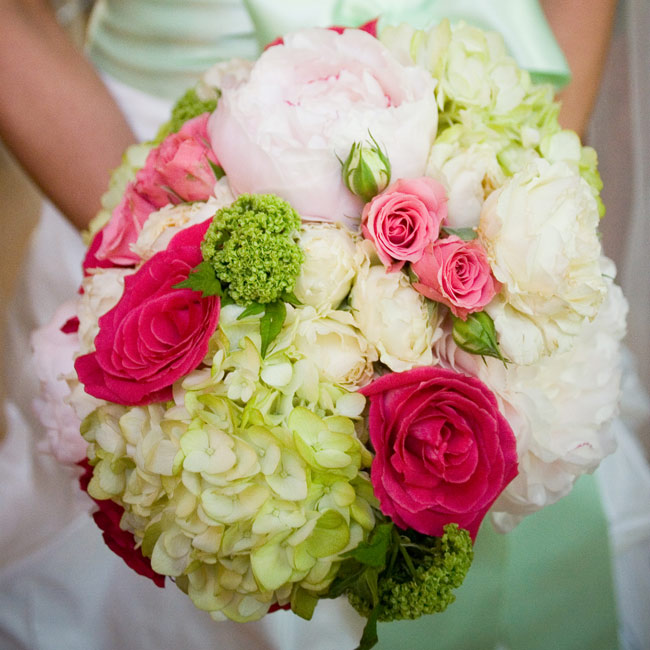 "Lauren carried a bouquet of ivory peonies, light green hydrangeas, ivory and dark pink–edged Rossini roses, green viburnum, and pink spray roses. ""My favorite part about my bouquet is that it was wrapped with a piece from my dress' sash, so it coordinated perfectly and made a special keepsake,"" Lauren says."
