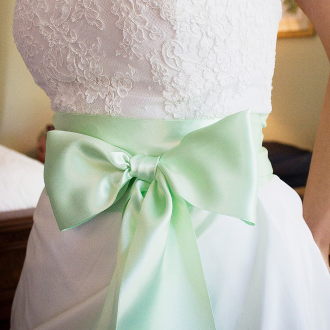 The bride wore a strapless, A-line gown with a pick-up skirt accented with a honeydew-colored satin sash by Jasmine Couture.