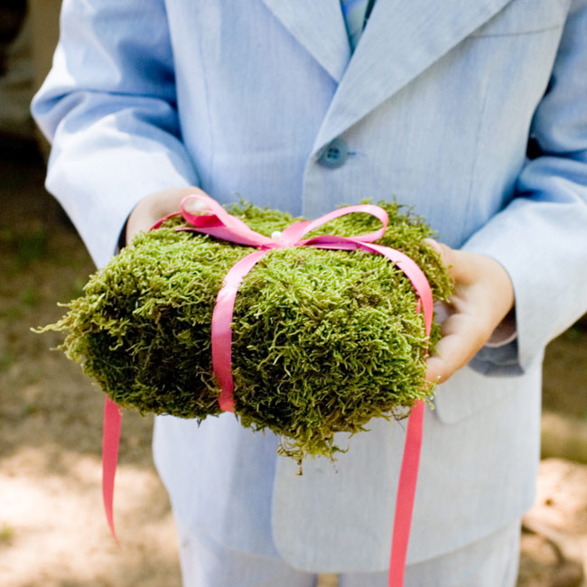 The ring bearer carried a moss-covered cushion tied with a pink satin ribbon.