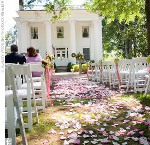 The couple exchanged vows on the lawn at the Madison Oaks Inn. White wooden chairs were set up for guests and ivory and pink rose petals were scattered along the aisle.