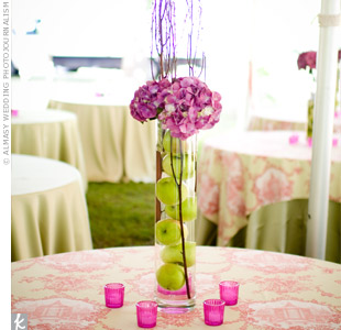 Tables were topped with two types of centerpieces. Some vases were composed of green apples with hot pink hydrangeas and birch branches, while moss-filled vases displayed the bridesmaid bouquets.