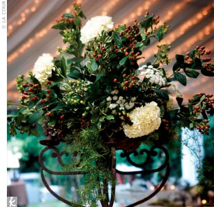 Short, iron centerpieces filled with antique white hydrangeas, red and green hypericum berries, Queen Anne's lace, pittosporum, and sedum gave each table a rustic feel.