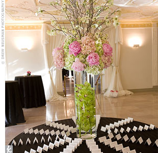 The escort cards -- which also incorporated the pink swirl motif -- were displayed on a table that included a dramatic centerpiece composed of six-foot-tall flowering dogwood branches, along with peonies and hydrangeas.