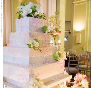The four-tiered square cake was covered in white buttercream and included the pink swirl design found on the stationery. The cake was also decorated with edible white pearls and white and green flowers and was displayed on a silver cake stand.