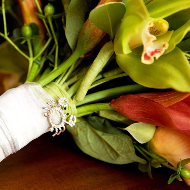 Nikki carried a round bouquet of green cymbidium orchids, green hypericum berries, orange circus roses, and mango calla lilies. A crab brooch -- symbolizing a term of endearment between the bride and groom -- was pinned to the ribbon wrapping the stems.