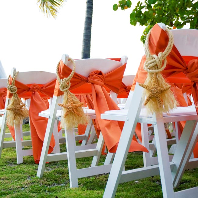 Guests sat in chairs tied with persimmon fabric, and end seats were adorned with rope and starfish.