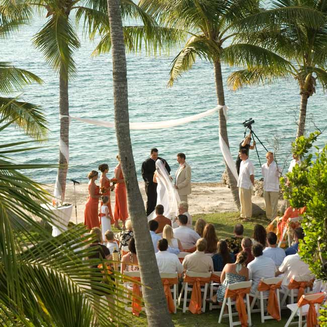 "Nikki and John exchanged vows just before sunset on the lawn at the groom's father's house. ""There were two palm trees at the end of the yard that framed the beautiful water view—that became our altar,"" the bride explains. To decorate, they tied sheer white fabric to the surrounding palms."