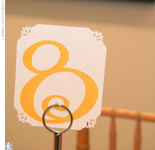 Mary used a quirky, curly font in bright yellow to tie the weddings signature accent color into the table numbers.