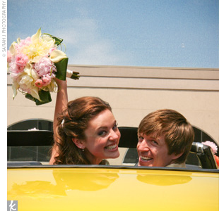 The newlyweds left their celebration in a bright yellow, 1971 Oldsmobile Cutlass. We really wanted to use a vintage car, and the Cutlass was perfect, says Mary. She decorated the vintage ride with coral pompoms.