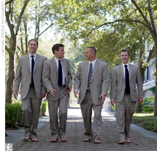 The guys looked dapper in taupe suits with white button-down shirts, navy silk shantung ties, and brown sandals with the University of Georgia G on the side to honor the couples alma mater. To stand out, Andy chose a navy-and-green striped tie.