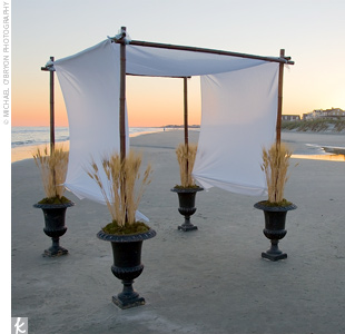 A large bamboo canopy draped in white linen was placed on the beach for the ceremony and was held in place by brown urns overflowing with sea grass.