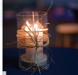 Glass cylinders wrapped with raffia were each filled with sand and a glowing white candle to add to the romantic, undersea feeling.