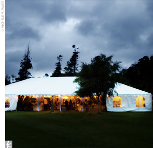 The reception tent was decorated with elegant fabric which created a sophisticated look. The couple also added drapery panels to form an entrance, and used the same fabric for table overlays. Curly willow, hanging votives, and a chandelier finished off the look.