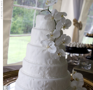 Krista and Brians all-white cake was decorated with a cascade of fresh, white orchids. Inside, the vanilla cake was filled with fresh preserves and berries, and whipped creme fraiche.