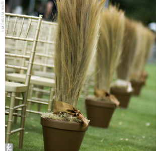 Large, grass-filled pots adorned the ceremony space. The terra cotta pots were painted gold, filled with bunches of faux grass, and tied off by a gold silk ribbon.
