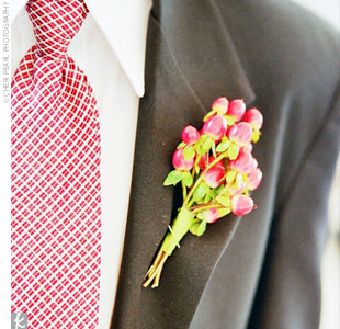 To complement the groomsmen's green hypericum berry boutonnieres, the ring bearer donned a red hypericum berry boutonniere on his lapel.