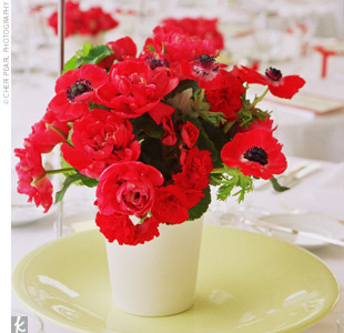 The centerpieces -- white, ceramic pots filled with a mix of red anemones and begonias -- provided a punch of color to the reception tables. Small glass votives were also placed around the arrangements to add ambience and light.