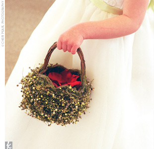 The flower girl dropped rose petals from a rustic basket covered with green hypericum berries. She wore a white dress with bead detailing on the bodice and a celadon green ribbon around her waist to match the bridesmaid dresses.