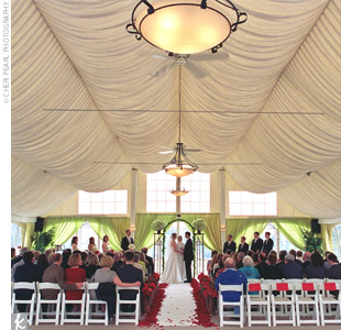 The ceremony took place beneath a fabric-draped tent on the golf club's terrace. Stefanie and Kevin stood beneath a rusted metal arch wrapped in green Smilax vines, flanked with two short, metal urns filled with green hydrangeas.