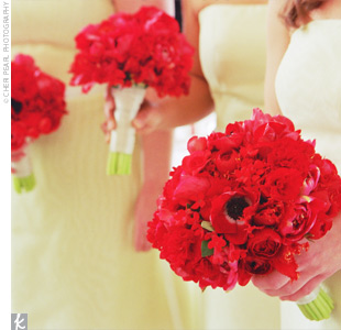 Stefanie's bridesmaids carried clusters of red spring flowers including tulips, anemones, ranunculus, begonias, and bouvardia, finished off with Midori sheer platinum ribbon.