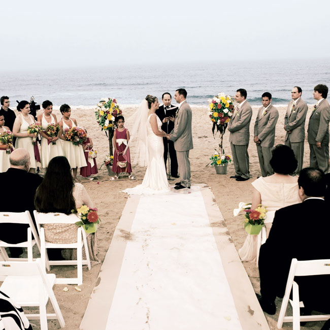 Victoria and Joseph married in a colorful wedding on the beach. White chairs accented with orange and yellow gerbera daisies lined the aisle, and the bride and groom stood between two bright pink, yellow, and orange floral topiary trees.