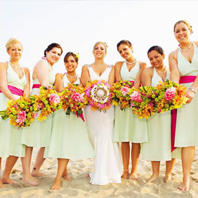 Victoria's six bridesmaids wore custom-made, green and white seersucker, halter dresses with a bright fuchsia sash. Their bouquets overflowed with Kermit mums, pink King Proteas, and orange stephanotis, bound with a colorful Lilly Pulitzer scarf.
