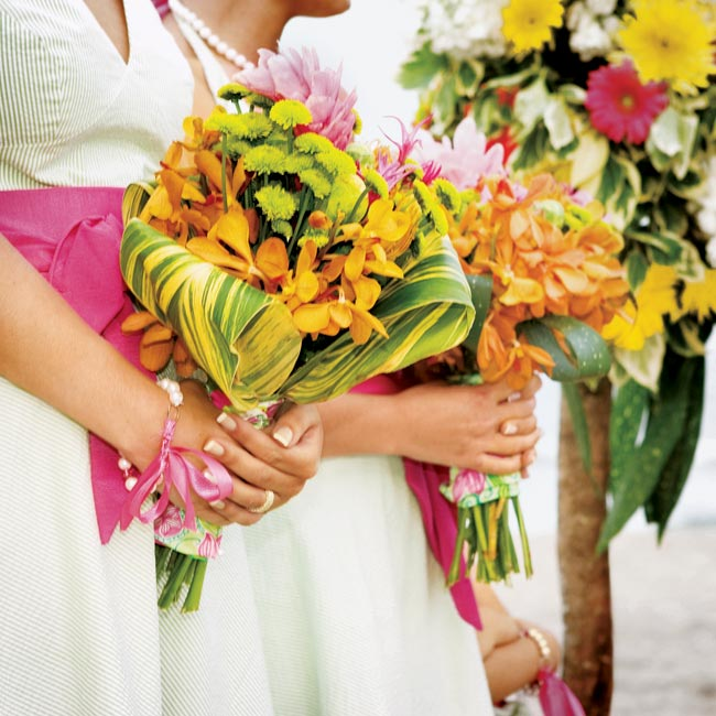 The bridesmaid bouquets overflowed with Kermit mums, pink King Proteas, and orange stephanotis, bound with colorful Lilly Pulitzer scarves.
