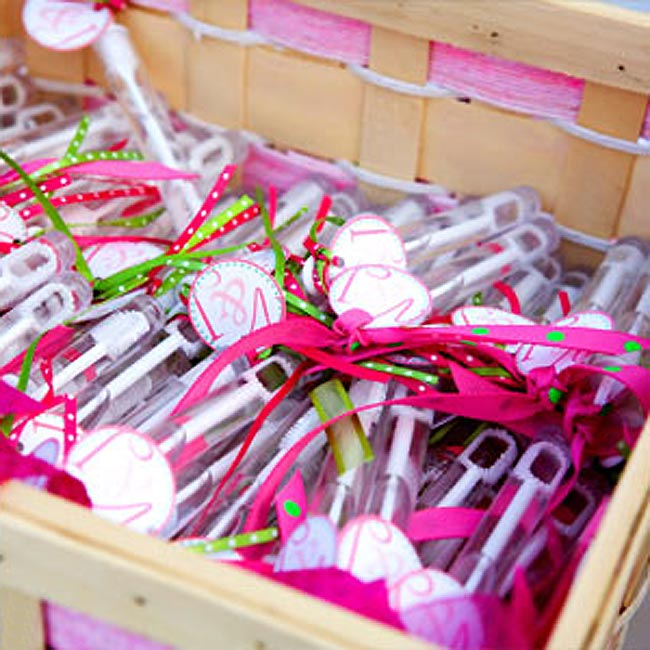 A woven, wooden basket held colorful, green and pink, bubble favors with V & J printed on tiny tags, which Victoria and Joseph's guests received at the ceremony. The bride also created tiny custom bottles of suntan lotion to go along with the couple's beach theme.
