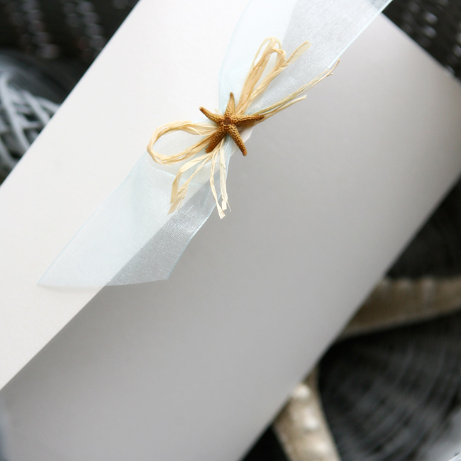 The couple tied in the beach theme (literally!) on their elegant formal invitations with an accent of gauzy white ribbon and a miniature starfish.