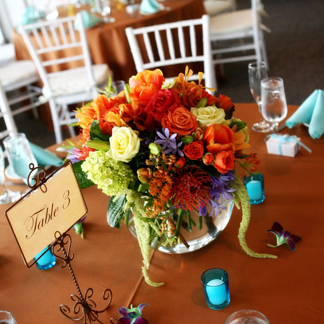 Echoing the bridesmaid bouquets, the centerpieces featured vibrant-colored orchids, roses, hydrangeas, and other exotic flowers.