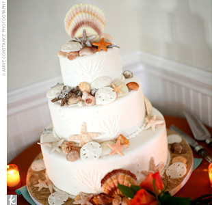 The white fondant-frosted wedding cake was accented with edible seashells and starfish that looked as if they had just been plucked from the sand.