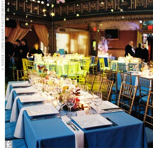 "The long rectangular tables at Mindy and Michael's reception were covered with bright blue table linens and set with sleek white chargers. The centerpieces were seasonal white, blue, periwinkle, lavender, and light yellow flowers with accents of orange blossoms, all tucked into sleek, 12-inch-square, aluminum dishes -- a signature David Beahm ""bio- ..."